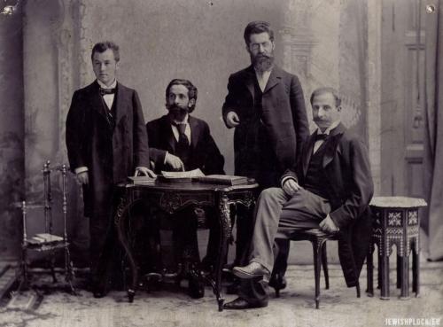 Od lewej Dr Siegfried Kalischer, Dr Edward Flatau (siedzi, wskazuje na książkę), Dr Louis Jacobsohn-Lask, Dr Bernhard Pollack (siedzi). Około roku 1900 w Berlinie. Z Archiwum rodziny Lask. Źródło: Wikipedia Commons (domena publiczna)